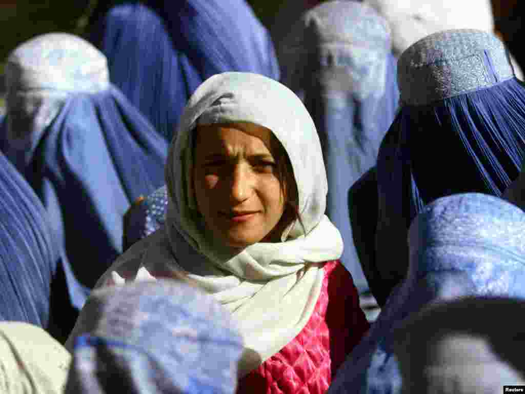 A young Afghan woman shows her face in public for the first time after 5 years of Taliban Sharia law as she waits at a food distribution centre in central Kabul November 14, 2001. Under its strict interpretation of Islam, the Taliban ordered all women hidden behind head-to-toe burqas. REUTERS/Yannis Behrakis