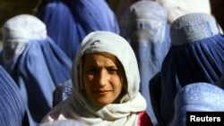A young Afghan woman shows her face in public for the first time after five years of Taliban rule in November 2001. Does the Koran really call for such standards of decency for women?