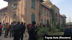 Police and rescue workers stand outside the Directorate of Agriculture Institute in Peshawar on December 1.