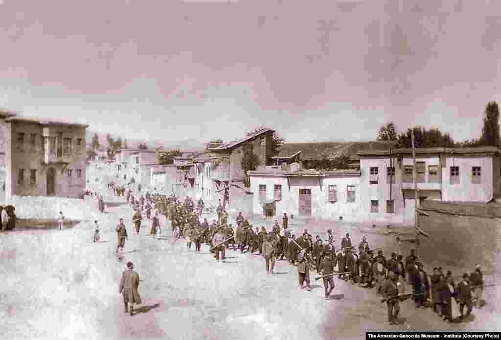 Fotografie înfățișând un grup de bărbați armeni deportați sub amenințarea armelor, în orașul Kharpert.