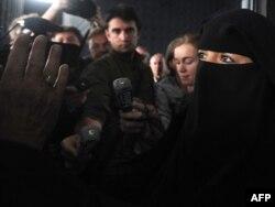 Fransada niqabla maşın sürdüyü üçün cərimə edilən müsəlman qadın Sandrine Moulleres (sağda) jurnalistlərin suallarını cavablandırır. Aprel 2010