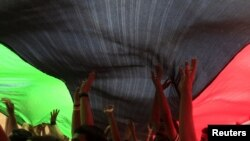 Ливиялыктар тобу Эл аралык кылмыш соту тарабынан Муаммар Каддафини камакка алуу тууралуу буйрук чыгарылганын угуп, шаттанууда. Бенгази ш., 2011-жылдын 27-июну.