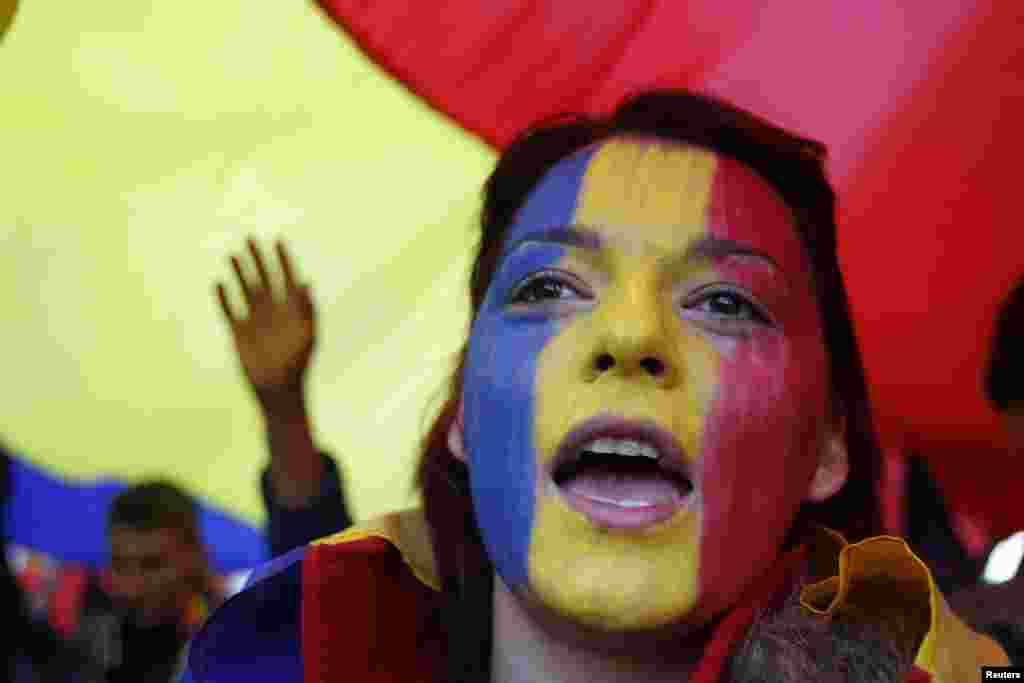 A woman with her face painted in the Romanian national colors shouts slogans during a march by Romanians and Moldovans through downtown Bucharest to demand the unification of Moldova and Romania. (Reuters/Bogdan Cristel)