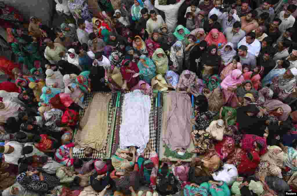 Relatives gather in Lahore, Pakistan, beside the bodies of victims of a suicide bomb attack on the Wagah border. (Reuters/Mohsin Raza)