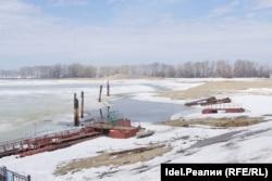А это уже — апрель 2012 года, то самое место, но другой ракурс. В центре кадра, между понтонами и сваями — полынья, полностью свободная ото льда, справа видны трубы канализации.