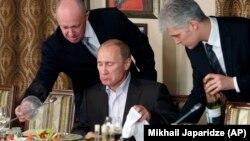 Російський бізнесмен, «кухар Путіна» Євген Пригожин (ліворуч) у своєму ресторані подає їжу Володимиру Путіну, 11 листопада 2011 року. Пригожина також називають засновником «фабрики тролів» у Петербурзі