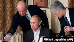 Yevgeni Priqojin (solda) Putinə xidmət göstərərkən