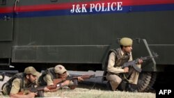 File photo of Indian police officials taking position behind a vehicle during an attack by militants on an army camp near Jammu in September 2013.