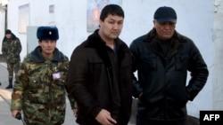 Подозреваемого Кадыра Досонова (в центре) ведут в тюрьму. Ош, 20 января 2012 года.