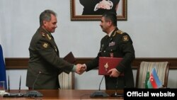 Azerbaijan - Defense Minister Zakir Hasanov (R) and his visiting Russian counterpart Sergey Shoygu sign an agreement after talks in Baku, 13 Oct2014
