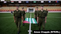Abkhaz soldiers practicing flag-raising as part of preparations for the Conifa soccer tournament, which kicks off in the Georgian breakaway region on May 28.