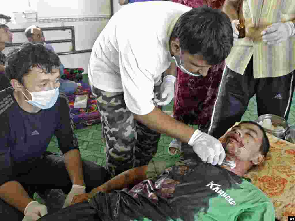 A doctor tries to save the life of a man wounded during ethnic clashes in the city of Osh on June 13.