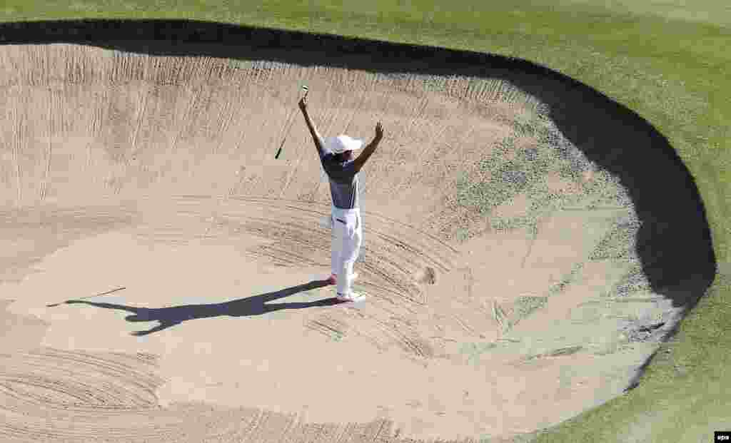 C.T. Pan of Taiwan reacts after making a shot during the men's golf tournament.