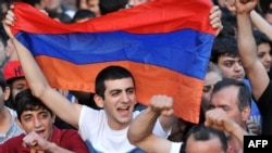 A demonstrator holds an Armenian flag as others shout slogans during a protest against an increase on electricity prices in Yerevan on June 25.