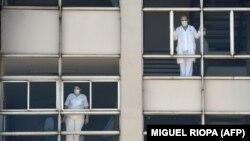 Medicinski radnici gledaju kroz prozore bolnice u Korunji, Španija, 26. mart