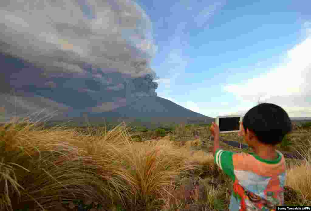 A boy takes pictures during an eruption of Mt. Agung on Indonesia's resort island of Bali. The eruption stranded tens of thousands of tourists after the ash cloud prevented planes from taking off. (AFP/Sonny Tumbelaka)