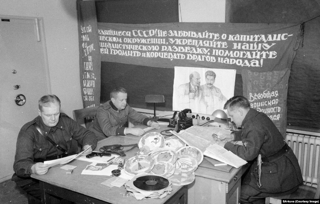 """Finnish officers with seized Soviet propaganda. The banner says, """"Workers of the U.S.S.R.! Do not forget about capitalist encirclement. Strengthen our socialist intelligence [service and] help it destroy and uproot enemies of the people!"""""""