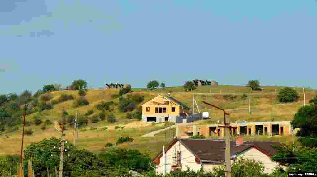 Здалеку на пагорбі над дачним кооперативом видно дві вежі батареї №30
