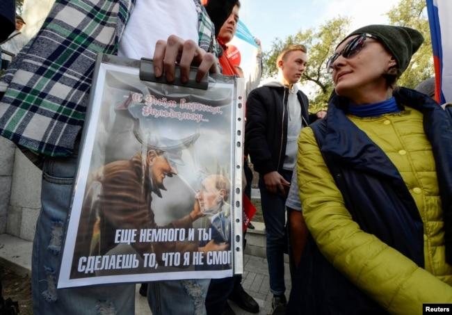 Плакат із зображенням президента Росії Володимира Путіна та Адольфа Гітлера на мітингу у Владивостоці, 7 жовтня 2017 року