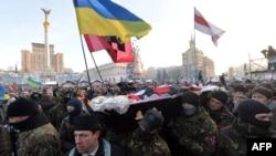Демонстранты несут гроб с телом Михаила Жизневского во время похоронной церемонии на площади Независимости. Киев, 26 января 2014 года.
