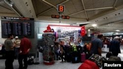 Пасажыры ў аэрапорце Стамбула, на наступны дзень пасьля тэракту, калі праца аэрапорту была адноўленая