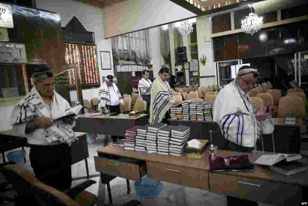 Iranian Jews read from the Torah during morning prayers at the Yussef Abad Synagogue.