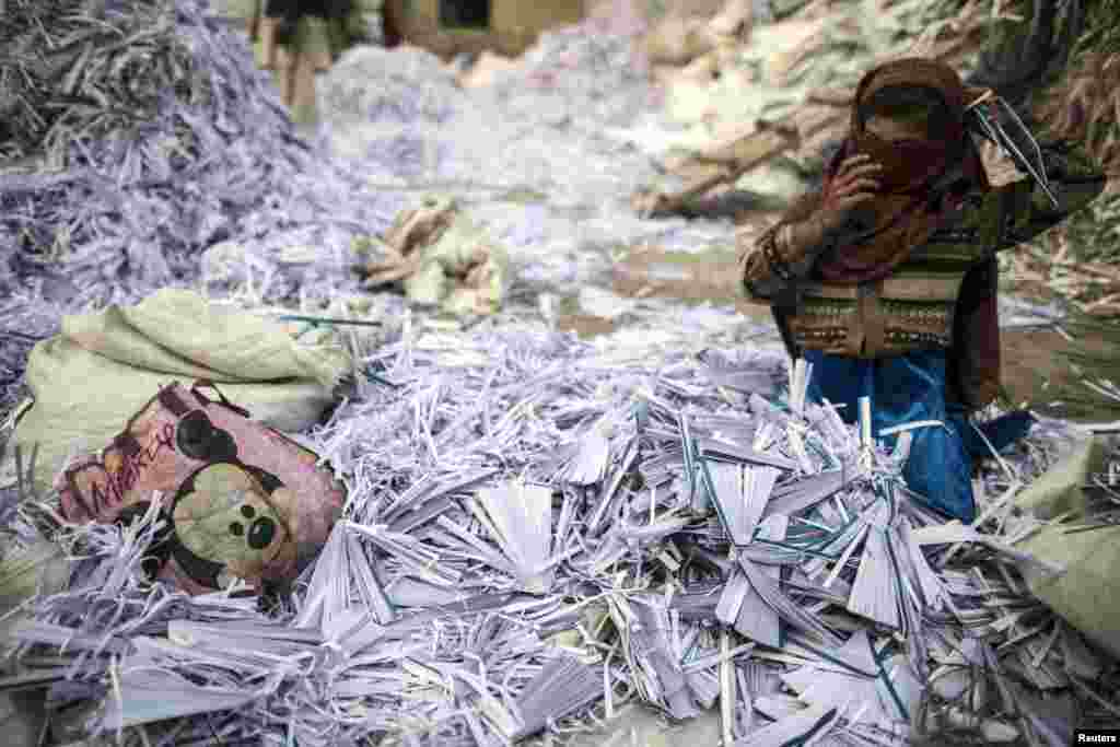 Razia, 9, fixes her scarf as she sorts papers before they are taken to a factory to be recycled in Lahore, Pakistan. (Reuters/Zohra Bensemra)