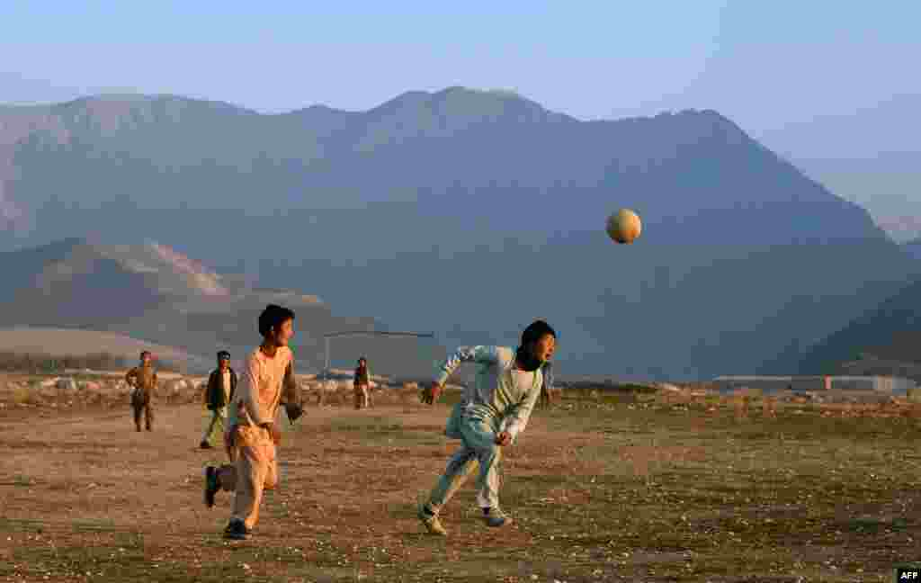 Afghan children play football in a field in a village on the outskirts of Mazar-e Sharif. (AFP/​Farshad Usyan)
