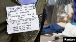 پیام یکی از پناهجویان کمپ ستالینگراد که در عقب یک خیمه نصب شده است.