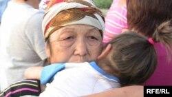 Немересін құшақтап тұрған әйел. Алматы, 23 шілде 2009 жыл. Көрнекі сурет