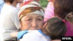 Бала құшақтаған қазақ әйелі Шаңырақтағы тағы бір толқу орнында. Алматы, 23 шілде 2009 жыл.