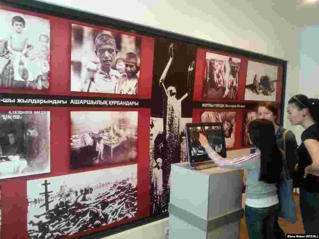 Девушки рассматривают стенды и читают информацию в электронном виде про жертв Голода 1930 годов. Музей жертв политических репрессий в Карагандинской области.