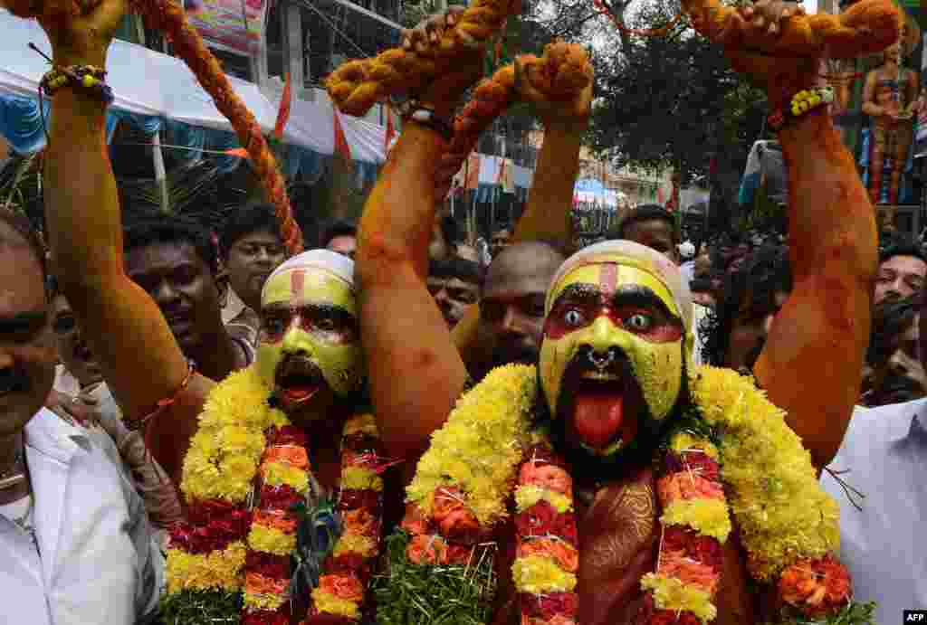 Indian Hindu devotees representing Potharaju, brother of the goddess Mahankali, dance in the streets during the Bonalu festival at the Sri Ujjaini Mahakali Temple in Secunderabad, the twin city of Hyderabad. (AFP/Noah Seelam)