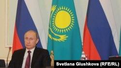 Президент России Вдалимир Путин на фоне государственных флагов Казахстана и России. Архивное фото.