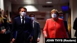 Cancelarul Angela Merkel și președintele Franței, Emmanuel Macron, îndreptându-se spre conferința de presă de la finalul summit-ului UE