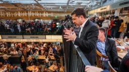 """Volodymyr Zelenskiy speaks to someone below during his """"press marathon"""" at a food market in Kyiv on October 10."""