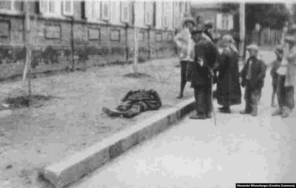 Харьков көшелерінің бірінде жүргіншілер аштан өлген адамның мүрдесінің жанында тұр.