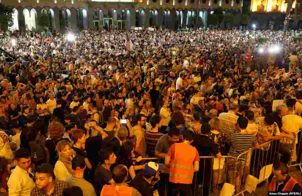 As night fell, protesters gathered outside the parliament building...