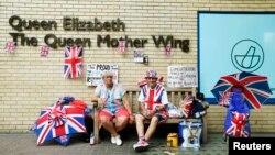 Британ ханзадасы Уильям мен жұбайы Кейт Мидлтоның тұңғыш баласы дүниеге келген емхананың қасында отырған адамдар. Лондон, 16 шілде 2013 жыл.