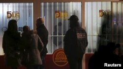 Forensic personnel are seen in front of a betting shop, the scene of a shooting that killed two soldiers and wounded five people.
