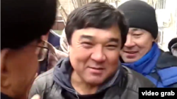 Ыкылас Кабдуакасов (в центре), приговоренный к ограничению свободы по обвинению в разжигании розни, у здания суда. Астана, 9 ноября 2015 года.