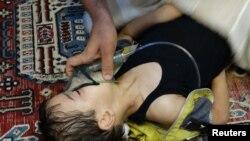 Дәрігер уланған балаға отттегі жұтқызып жатыр. Сирия, 21 тамыз 2013 жыл.
