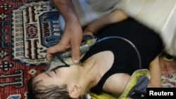 A boy, affected by what activists say is nerve gas, breathes through an oxygen mask in the Damascus suburb of Saqba in August 2013.