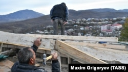 NAGORNO-KARABAKH - Local residents repair a roof with construction supplies brought from Russia as humanitarian aid, November 25, 2020.
