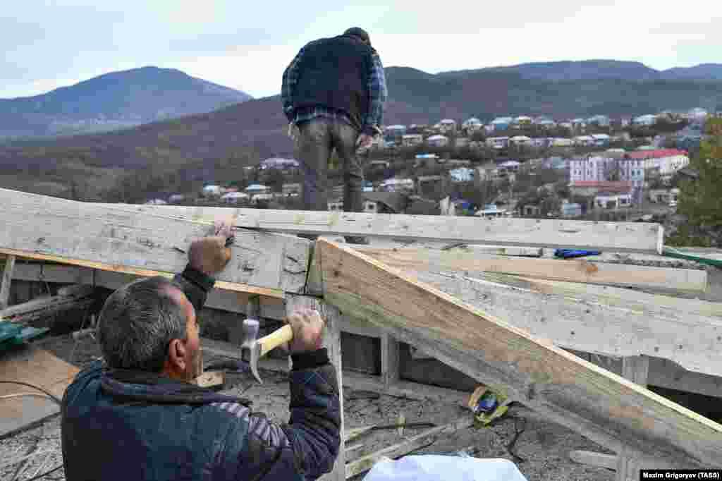 Жители ремонтируют дом, поврежденный при обстрелах. В ходе боев и ракетных обстрелов были убиты десятки мирных жителей с обеих сторон конфликта.
