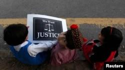 Дети сидят с плакатом в руках на обочине дороги во время акции протеста, организованной после изнасилования ребенка в Лахоре. Исламабад, 17 сентября 2013 года.
