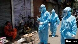 Қорғаныш киім киген медицина қызметкерлері тұрғындармен сөйлесіп тұр. Үндістан, 7 маусым 2020 жыл.
