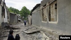 Ethnic Uzbeks on a street in the village of Vlksm, destroyed during recent clashes in Kyrgyzstan.