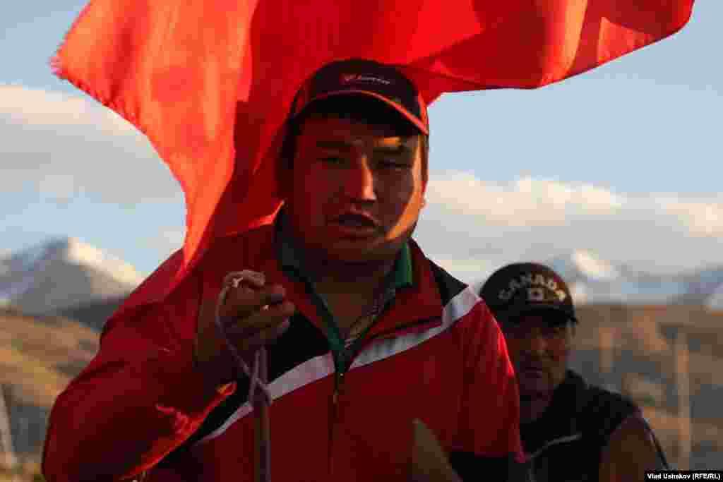 A protester carries a Kyrgyz flag.
