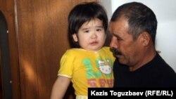 Жаймухан Кушеров, отец 32-летнего Джанабергена Кушерова, погибшего в дни декабрьских событий в Жанаозене, со своей трехлетней внучкой Мариам. Поселок Тенге Мангистауской области, 16 февраля 2012 года.